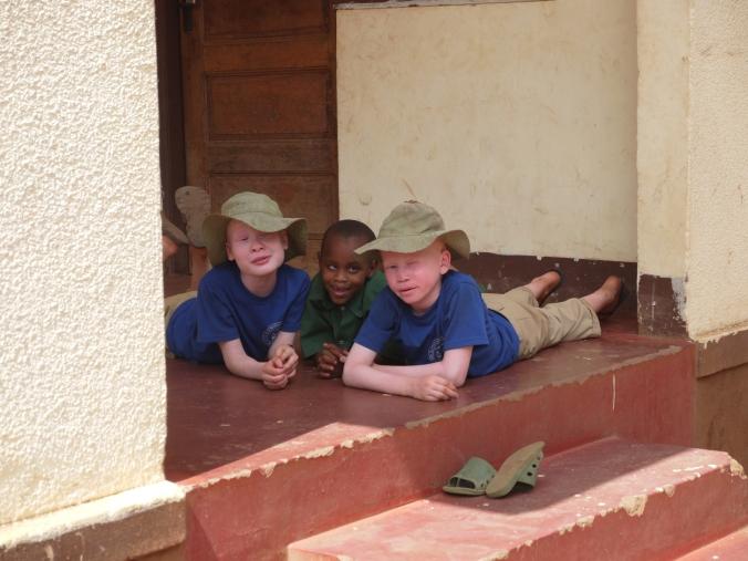 Mwereni scholieren spelen in de schaduw